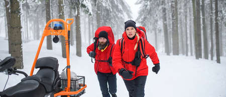 Paramedics from mountain rescue service provide operation outdoors in winter in forest.