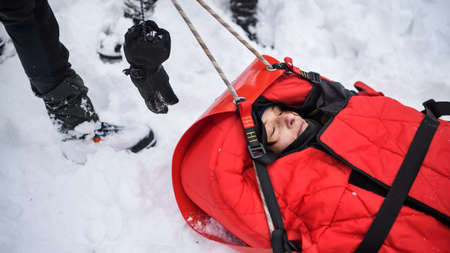 Mountain rescue service provide operation outdoors in winter in forest, pulling injured person in stretcher.