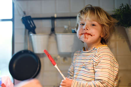Small boy indoors in kitchen at home, helping with cooking. Standard-Bild