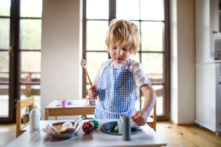Small boy with apron playing indoors with toy kitchen at home.