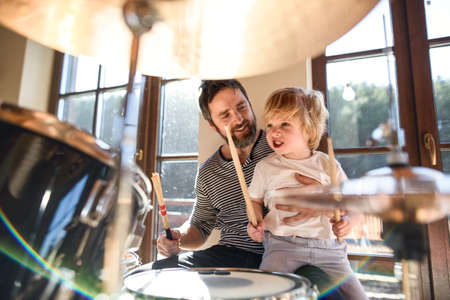 Small boy with father indoors at home, playing drums.