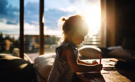 Small girl drawing pictures in wooden cabin, holiday in nature concept. 免版税图像