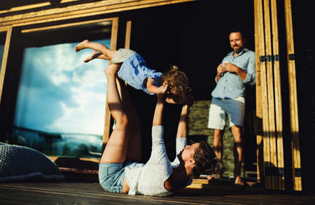 Family with small daughter having fun on patio of wooden cabin, holiday in nature concept. Standard-Bild