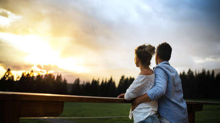 Rear view of couple standing on patio of wooden cabin at sunset, holiday in nature concept. 免版税图像