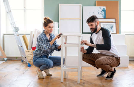 Mid adults couple renovating furniture indoors at home, relocation and diy concept.