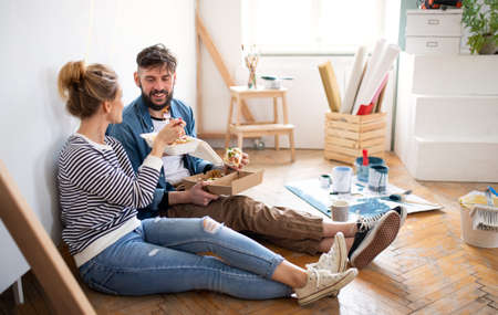 Couple eating lunch indoors at home, relocation, diy and food delivery concept.