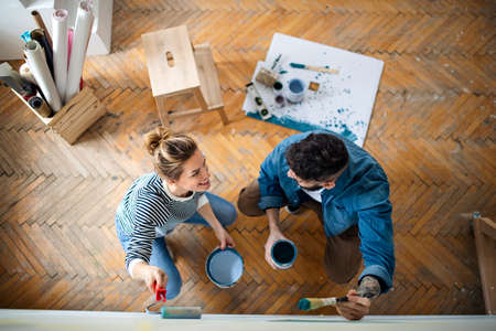 Top view of couple painting wall indoors at home, relocation and diy concept. 免版税图像