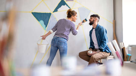 Couple having fun when painting wall indoors at home, relocation and diy concept.