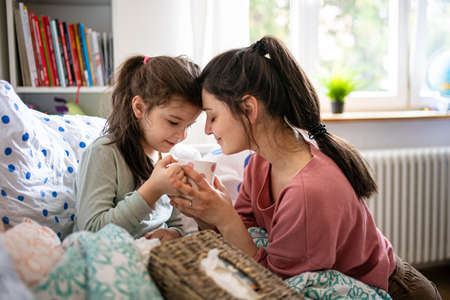 Mother looking after sick small daughter in bed at home. 免版税图像