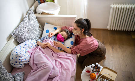 Top view of mother looking after sick small daughter in bed at home, concept.