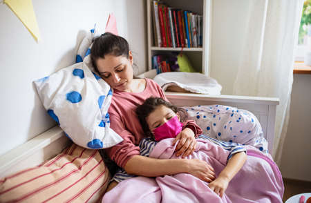 Tired mother looking after sick small daughter in bed at home, concept.