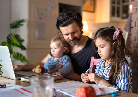 Father with small daughters in kitchen, distance learning, home office and schooling concept. 免版税图像