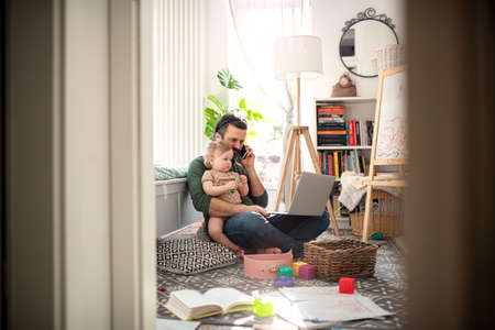 Father working with small toddler daughter in bedroom home office concept.