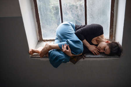 Woman lying on old and dirty window sill, solitude, mental health and depression concept.