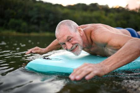 Senior man on paddleboard on lake in summer, swimming.