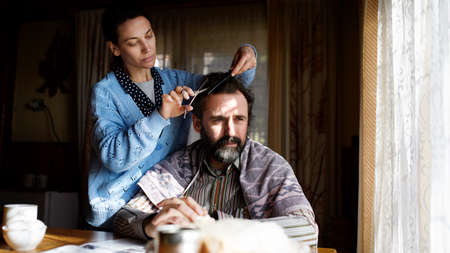 Portrait of poor woman cutting husbands hair indoors at home, poverty concept.