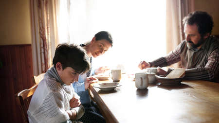 Angry small girl with parents sulking indoors at the table at home, poverty concept. Standard-Bild