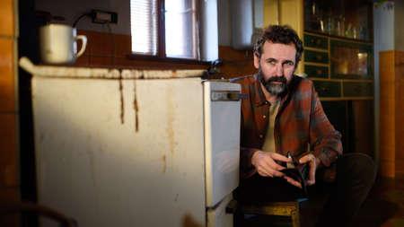 Portrait of poor mature man with empty wallet indoors at home, poverty concept. Standard-Bild