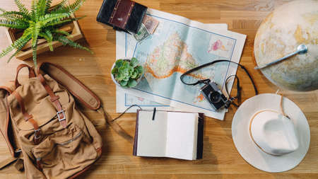 Flat lay top view desktop travel concept with laptop, maps and other travel essentials.