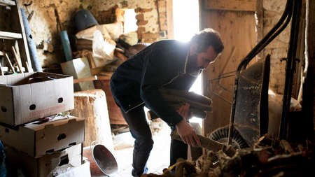 Poor mature man gathering firewood at home, poverty concept. Standard-Bild