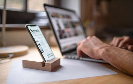 Smartphone in wooden stand holder on table indoors at home or on office. 免版税图像