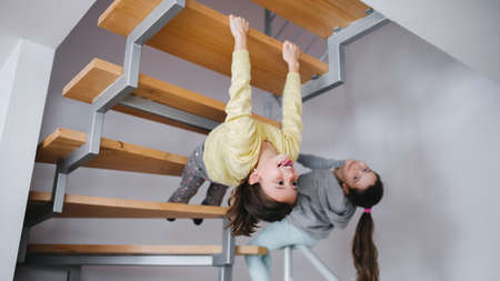 Two small girls sisters indoors at home, having fun under staircase. 免版税图像