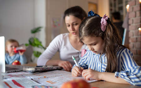 Mother with small daughter in kitchen, home schooling and distance learning concept. Standard-Bild