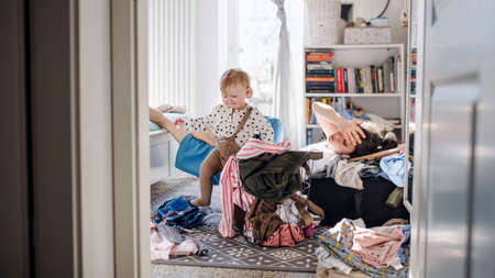 Tired mother with small toddler daughter in messy bedroom at home, resting. 免版税图像
