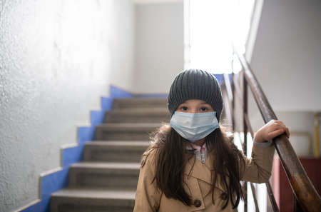 Small girl with face mask walking down the stairs in block of flats