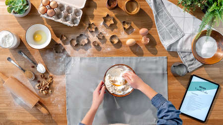 Top view of unrecognizable woman baking biscuits, desktop concept.