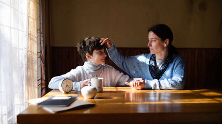 Portrait of sad poor mature mother with small daughter indoors at home, poverty concept. 免版税图像