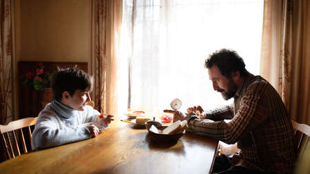 Portrait of poor small girl with father eating indoors at home, poverty concept. 免版税图像