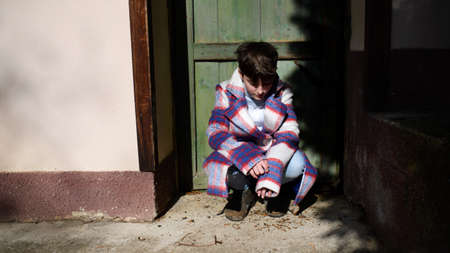 Poor sad small girl with large coat outdoors in front of house, poverty concept.