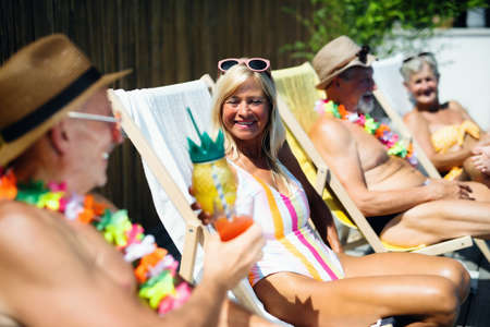 Group of cheerful seniors sitting by swimming pool outdoors in backyard.