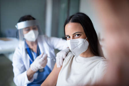 Woman with face mask getting vaccinated and taking selfie in hospital, virus and vaccination concept. Foto de archivo