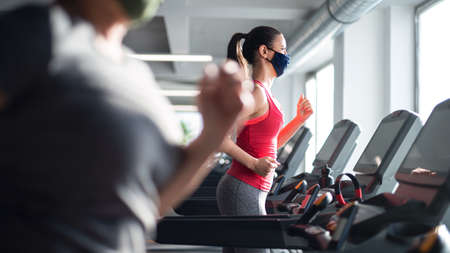 Woman with face mask doing exercise on treadmill in gym, virus concept.