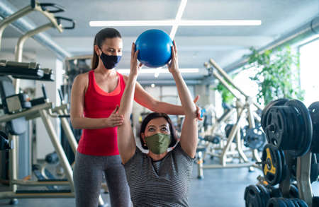 Senior woman with personal trainer doing exercise in gym,  virus concept.