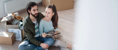 Top view of young couple moving in new flat, new home and relocation concept.