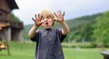 Small boy with dirty hands standing in vegetable garden, sustainable lifestyle.