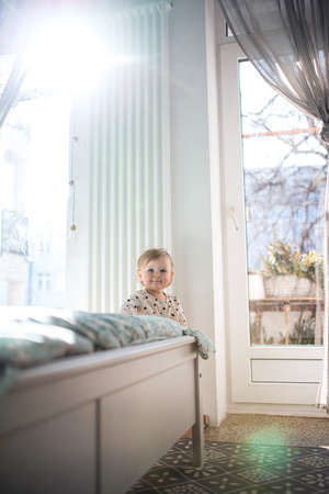Small toddler girl walking by bed in bedroom at home, first steps concept. Foto de archivo