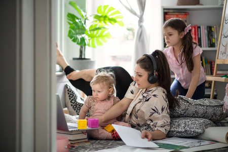 Mother working with small daughters in bedroom, home office concept.