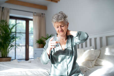 Senior woman with neck pain getting up from bed in the morning, health problems concept.