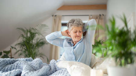 Senior woman in bed at home getting up in the morning.