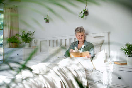 Happy senior woman reading book in bed at home.