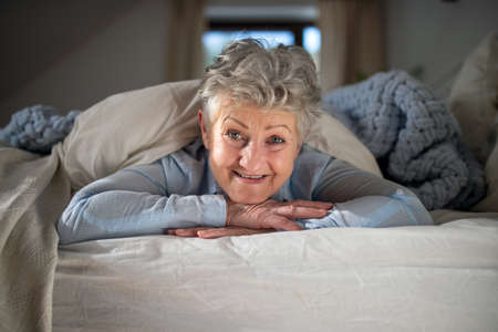 Happy senior woman in bed at home, looking at camera.