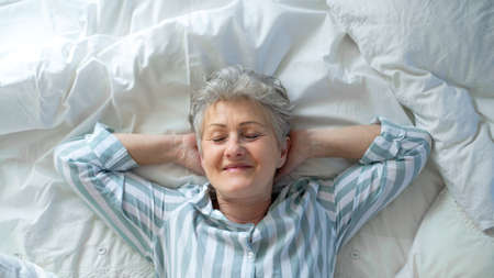 Top view of happy senior woman in bed at home, eyes closed. Foto de archivo