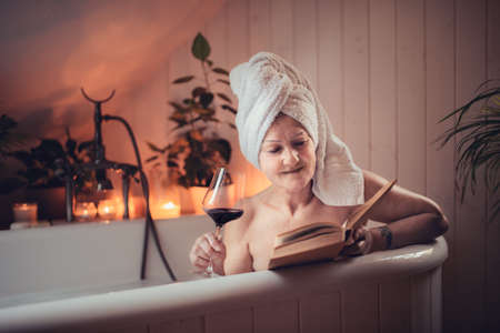 Happy senior woman reading book and drinking wine in bath tub at home.