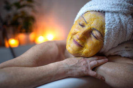 Happy senior woman with beauty face mask in bath tub at home, relaxing.