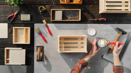 Top view of unrecognizable woman making wooden boxes, small business and desktop concept.