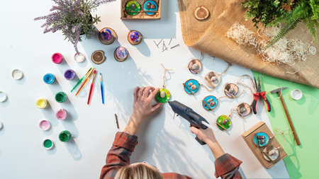 Top view of craftswoman making diy decorations, small business and desktop concept.